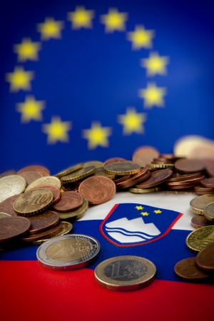 Slovenian flag against European Union flag with Euro coins scattered over  Stock Photo