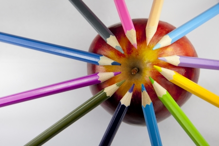 Color pencils forming a circle with their tips on a red and yellow apple against a white background