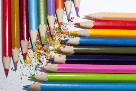 Colorful pencils  red, brown, blue, green, pink, orange, grey, violet       positioned in two columns facing each other at 90 dergees angle forming a diagonal between their points against a white backgroung sprinkled with colorful shavings