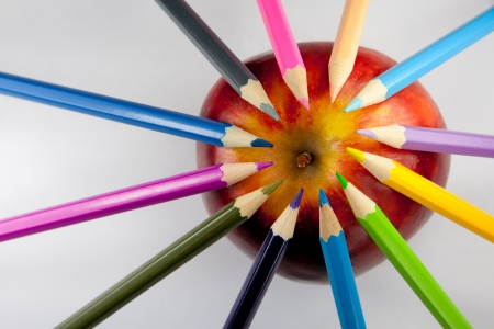 Color pencils forming a circle with their tips on a red and yellow apple against a white background.