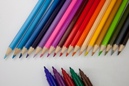 Sorted color pencils against sorted water color marker pens. Stock Photo