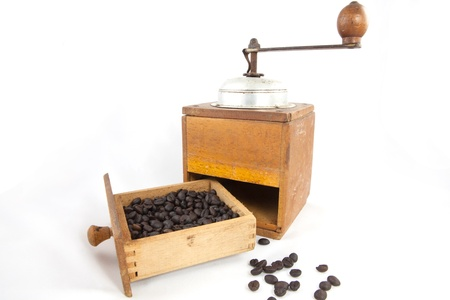 An old coffee grinder with coffee beans