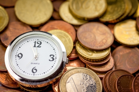 Euro coins and a clock showing 5 minutes until 12