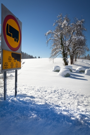 Traffic sign warns of snow and ice, on sunny and snowy day, with winter landscape in background