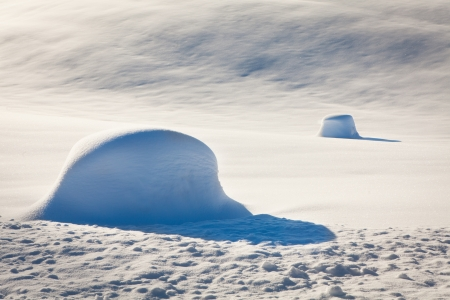 Snow piles on a snowy field, sun Stock Photo