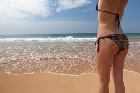 Perfect young women back on beach with black swimsuit and covered with sand