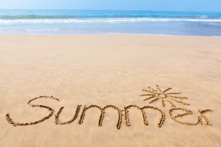 The Word Summer Written in the Sand on a Beach with Drawing of the Sun and with Sea in Background Stock Photo