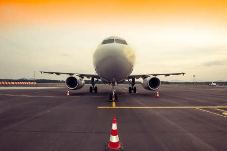 Commercial airplane parking at the airport - front, with traffic cone