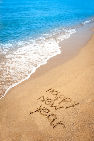 Happy new year written in sand, on tropical beach