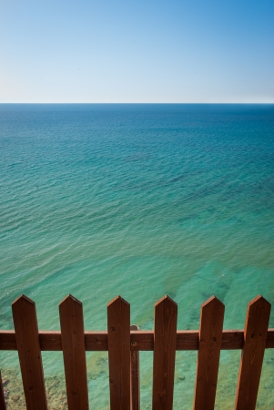 Wooden fence in front of beautiful turquoise sea in Corfu, Greece