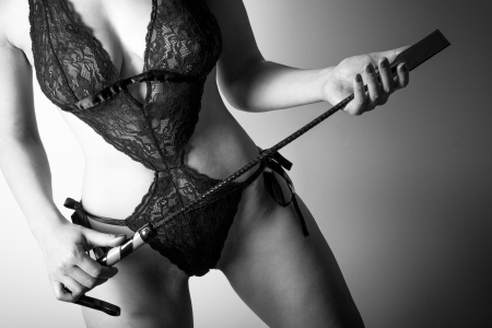 A young lady mistress in sexy lingerie with a leather whip - black and white phot Stock Photo - 19992057