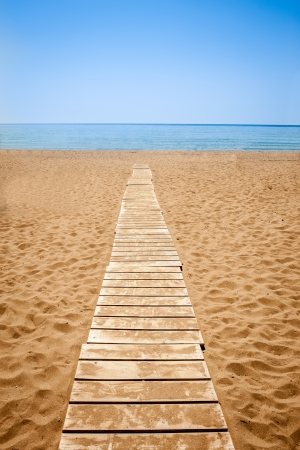 Wooden path to the sandy beach, Greece