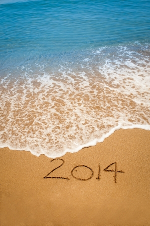 Year 2014 written in sand, on tropical beach