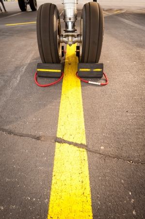 Airplane tires on yellow line, abstract transportation Stock Photo