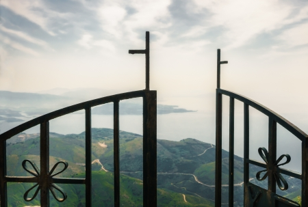Metal doors opened into the walley with sea and background and cross in top of them photo