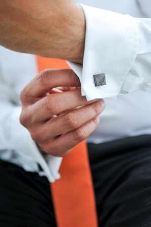 Close up of a mans (grooms) hand while fastening cuff