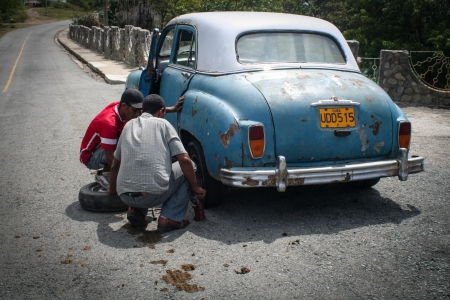 SIBONEY, CUBA - AUGUST 20  Unidentified men changing tyres on their old car, on August 20, 2007  Since embargo, Cuban cars cannot be mantained regularly  Editorial