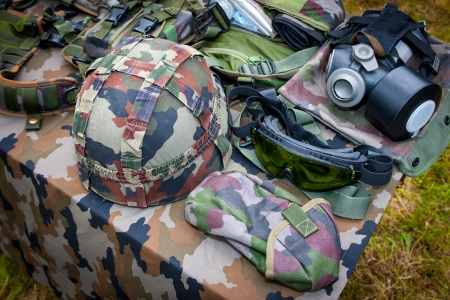 Basic military equipment with helmet, glasses and gas mask on the table Stock Photo