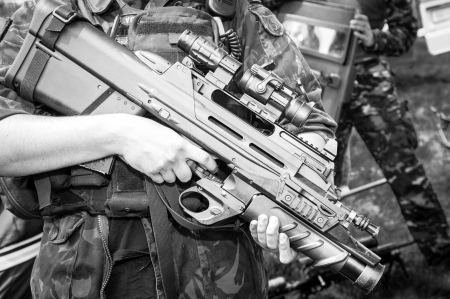 Soldier holding a machine gun in standing position, black and white close up
