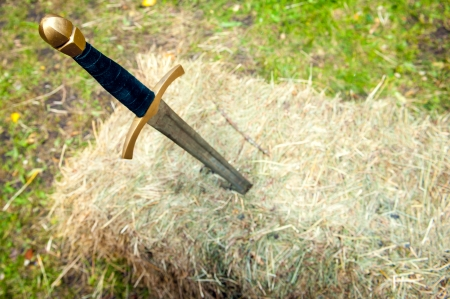 Medieval sword stuck in a pile of hay with blurred