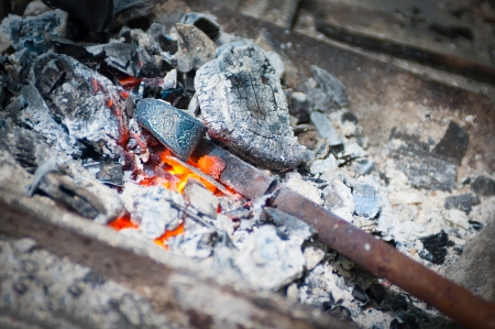 Iron stick in hammer furnace in glowing ember