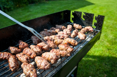 Balkan meatballs called cevapi on barbecue, with BBQ fork