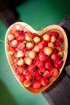Cherries in wooden dish on green background Stock Photo