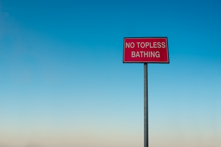 No topless bathing red sign in front of blue sky - background