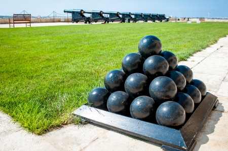 Old cannonballs stacked in pyramid, in front of blured cannons, on Valletta Castle, Malta