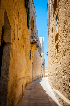 Typical tight street in Mdina, Malta with high stone walls of houses