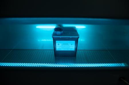 Box with danger virus content under ultravillet light Stock Photo