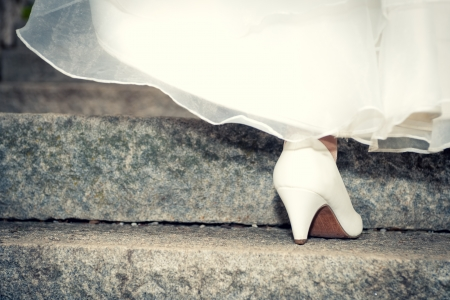 Bride in wedding shoes and dress on stairs, close up photo