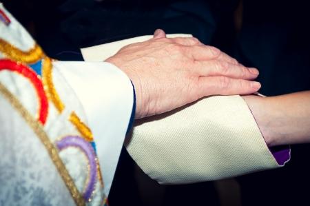 Catholic priest holding his hand on newlyweds Stock Photo