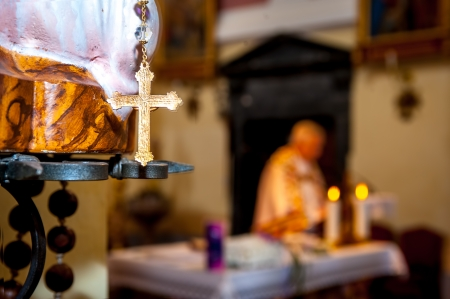 catholic wedding: Golden cross close up, with blurred priest, during the holy mass