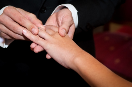 Groom putting wedding ring on bride s finger photo