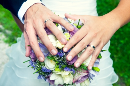 Hands and rings on wedding bouquet, close up Stock Photo