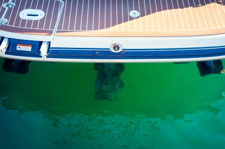 Sailboat stern with engine, on green water, sea Stock Photo