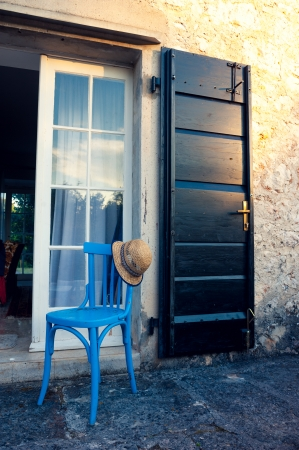 Summer hat on blue chair, in front of entrance in beautiful Provance house