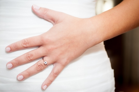 Bride with engagement ring holding her hand on wedding dress Stock Photo