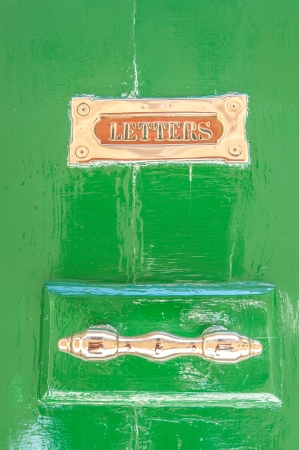 Green wooden door close-up with golden handle and slot for letters