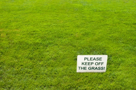 White Please keep off the grass sign on green grass