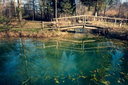 Wooden bridge over the river, in autumn Stock Photo