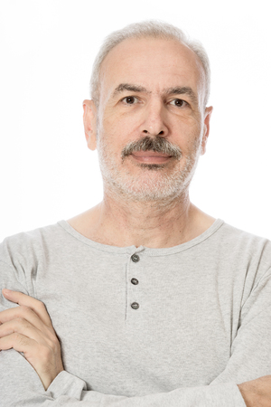 looking directly at camera: Close up portrait of a smiling attractive senior man looking directly at the camera with white background
