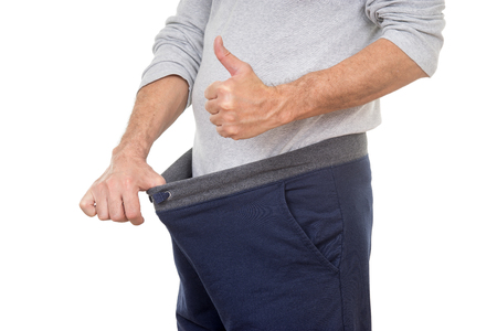 old man looking in his pants and showing thumbs up Фото со стока