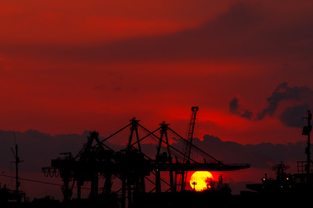 shipbuilder: Silhouette of an Industrial Dock Crane Unloading at Sunset. Izmir - Turkey