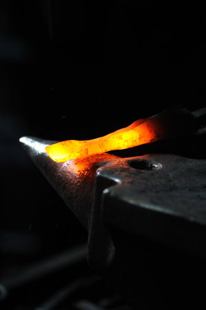 blacksmith: A blacksmith hammering a hot metal rod to shape it.