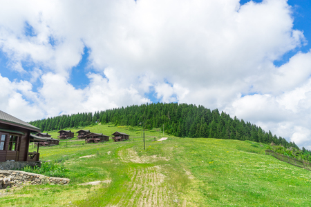 View of a wooden mountain cabin with mountains in the background Stock Photo