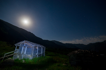 starry night: Creative Light painting of an abandoned wooden cabin in rural Artvin, Turkey with blue hour sky - wide angle view