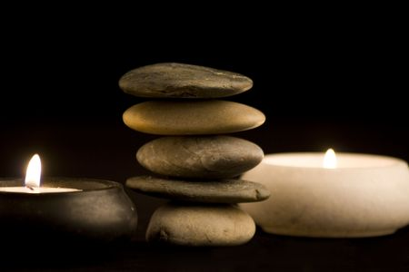 bath essence: Stack of spa stones and candles  in the dark