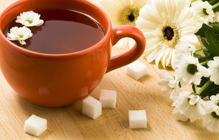 Cup of herbal tea, flowers and cubes of sugar on a wooden board photo